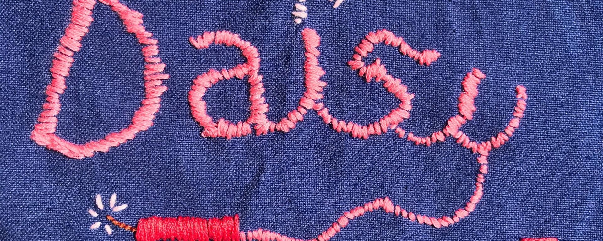 Pink embroidery on blue fabric with the name DAISY