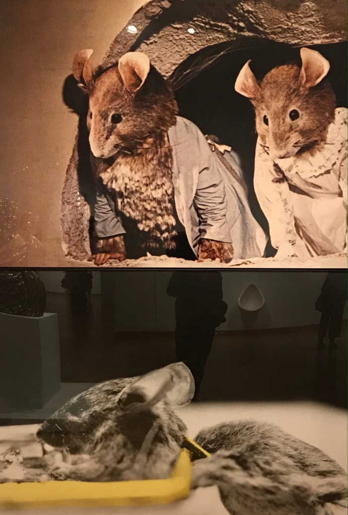 Artwork by John Baldessari showing two puppet mice overlooking a real dead mouse in a trap