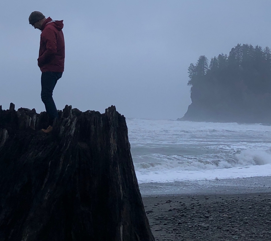 Artist Ray Monde standing on a giant stump at La Push, Washington