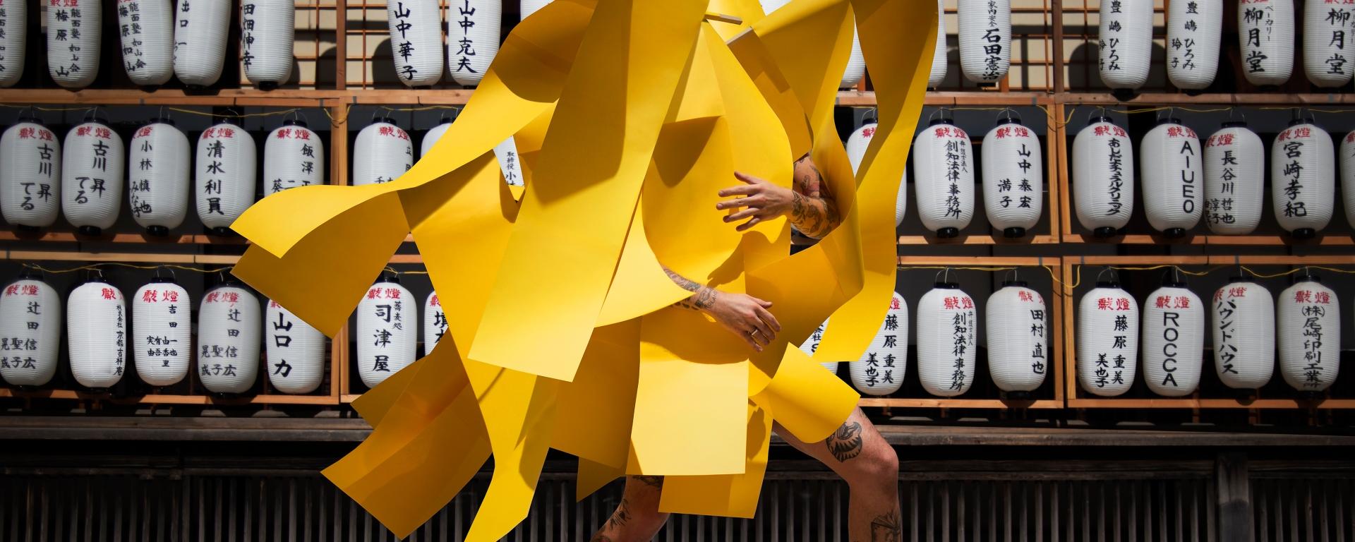 Image of artist Gerwyn Davies in yellow with japanese lantern