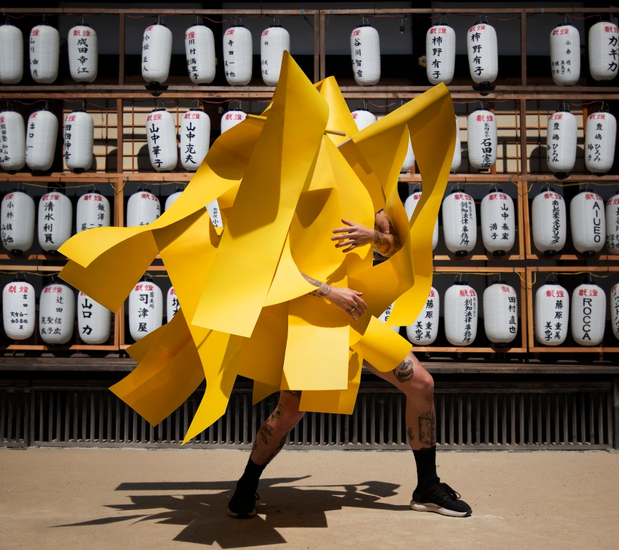 Image of artist Gerwyn Davies in yellow with japanese lantern